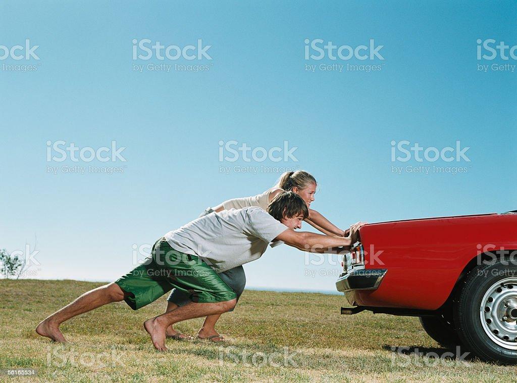 Couple pushing car stock photo