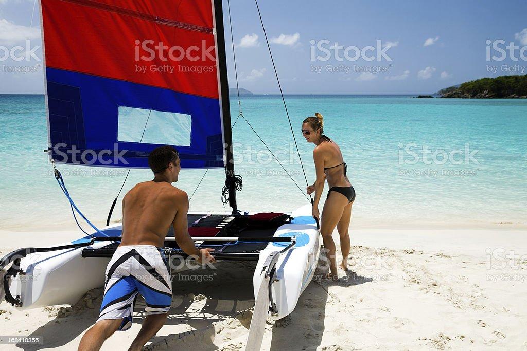 couple pushing catamaran into water to go sailing stock photo