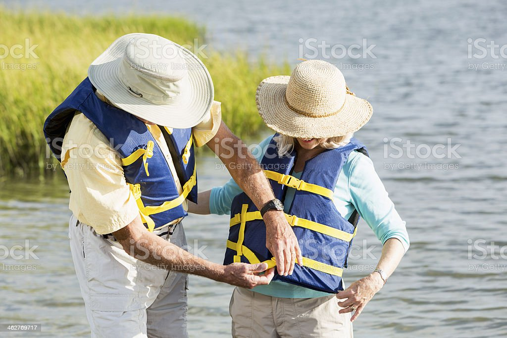 Couple putting on lifevests by water royalty-free stock photo