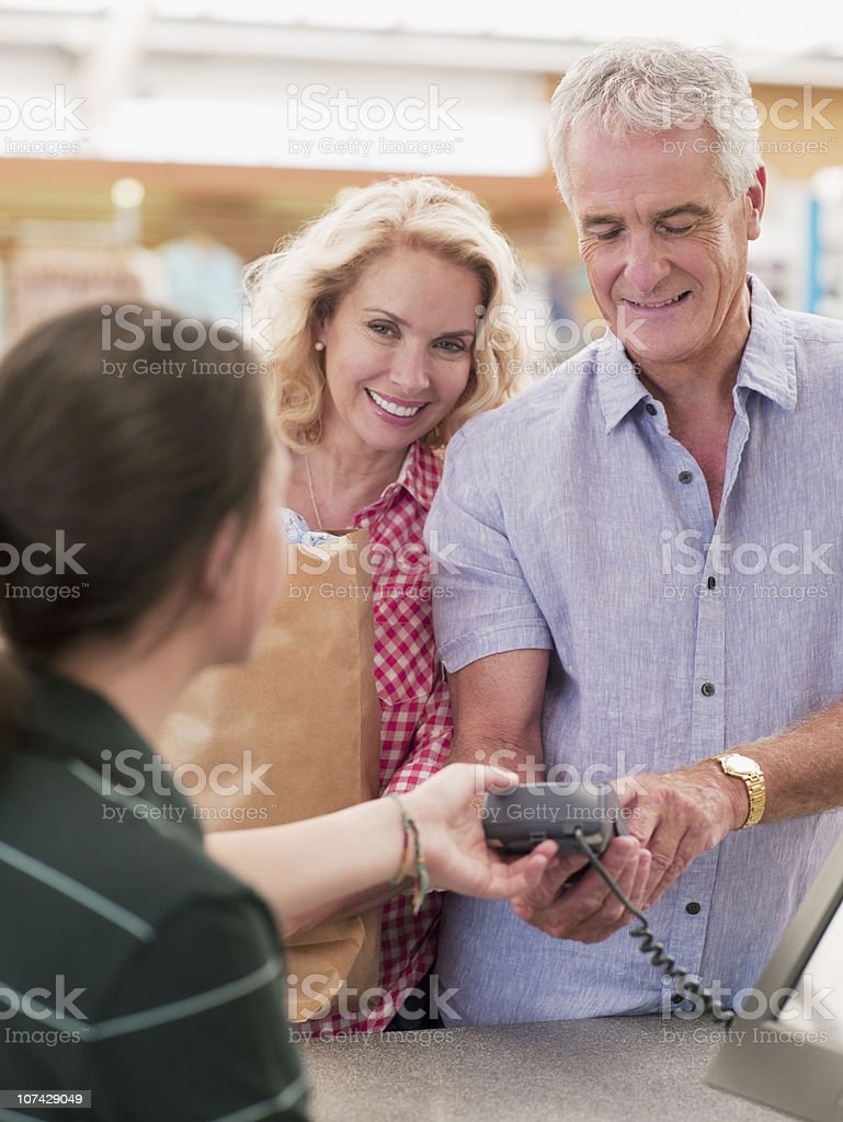 Couple putting PIN number into security device stock photo