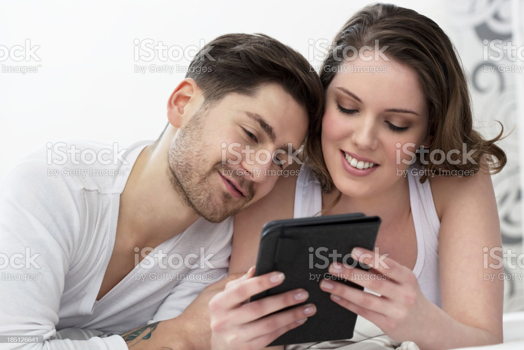 Couple Reading a Book on an E-Reader royalty-free stock photo