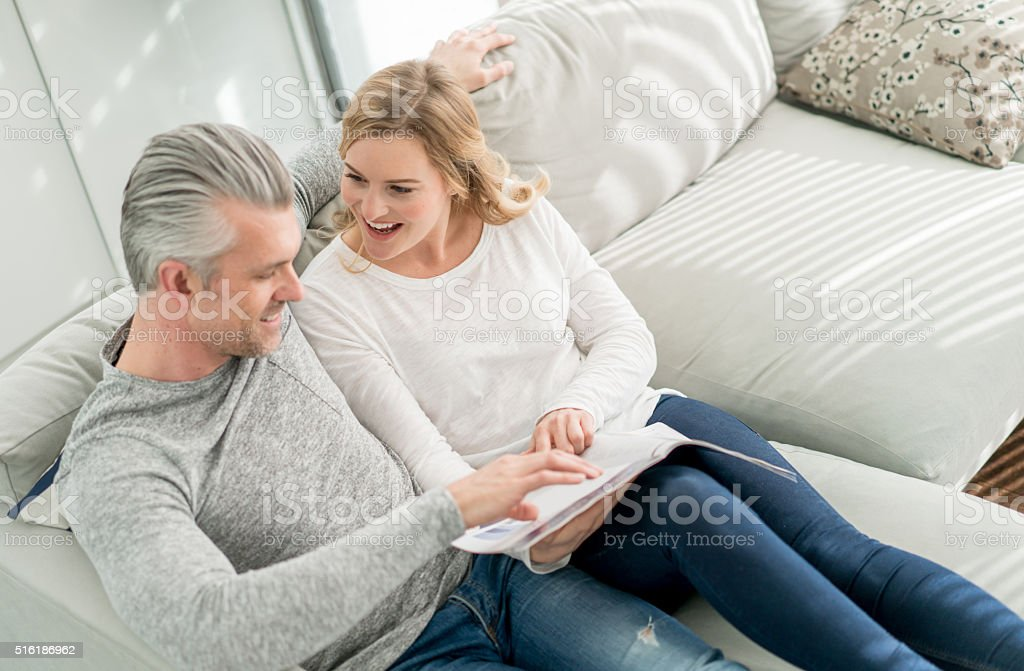 Couple reading a magazine at home stock photo