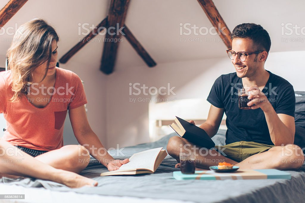 Couple reading book and having breakfast in bed stock photo