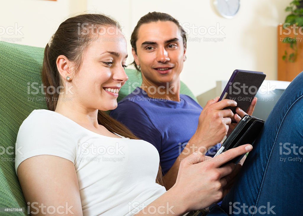 Couple reading eBooks at home stock photo