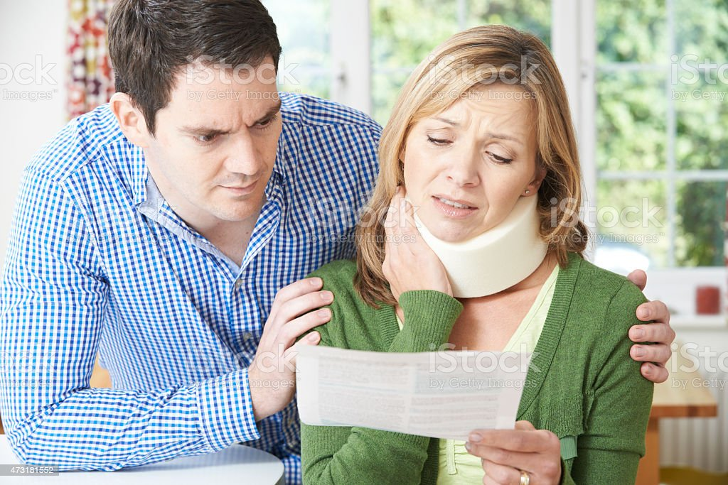 Couple Reading Letter In Respect Of Wife's Neck Injury stock photo
