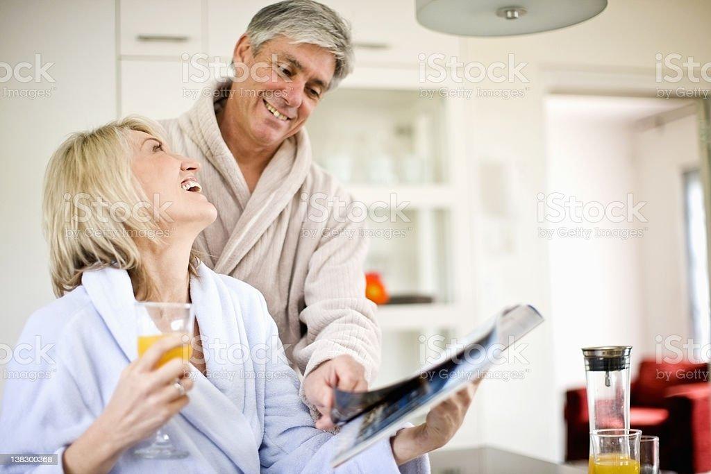 Couple reading magazine at breakfast royalty-free stock photo