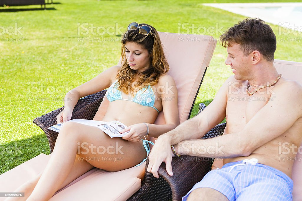 Couple Reading Magazine by the Poolside royalty-free stock photo
