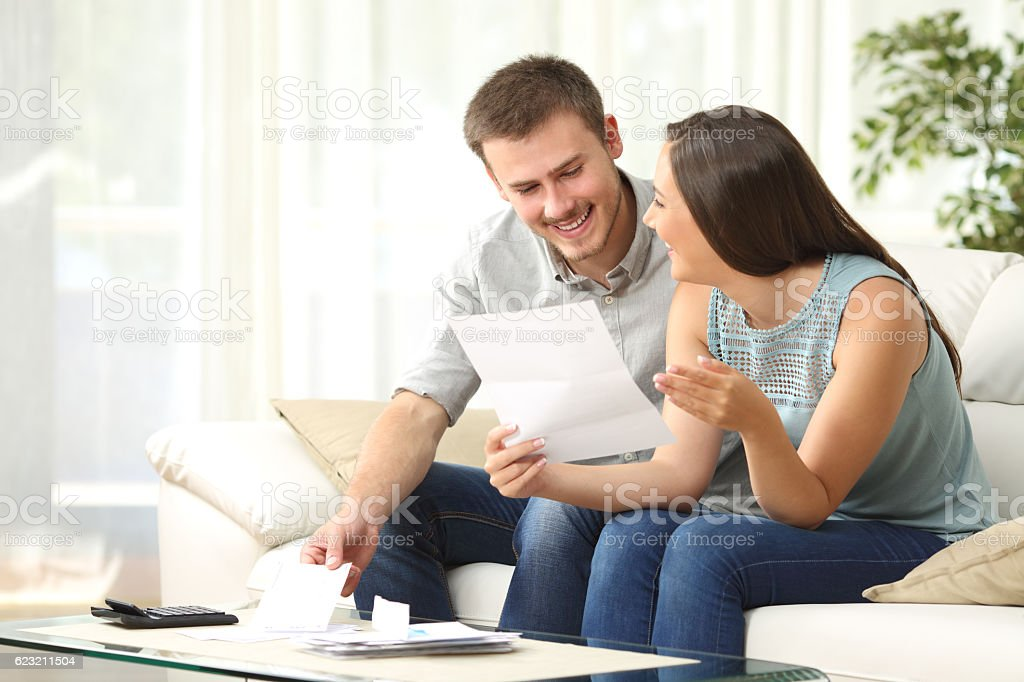 Couple reading mail at home stock photo