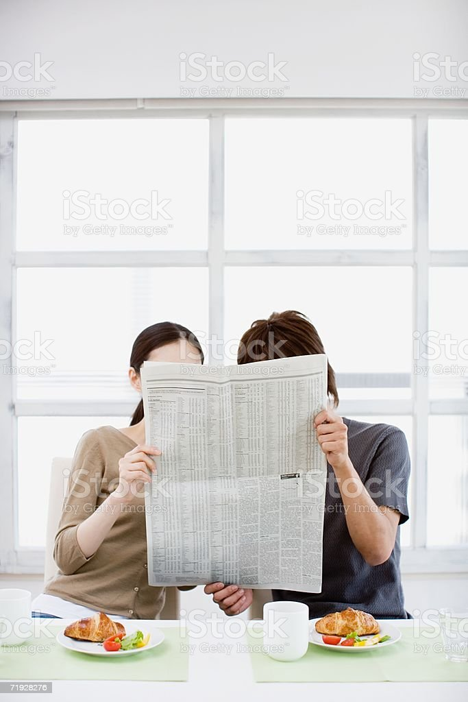 Couple reading morning newspaper together royalty-free stock photo
