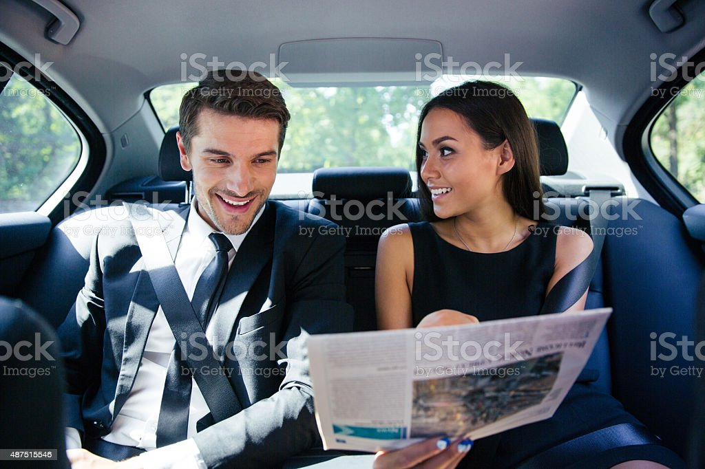 Couple reading newspaper in car stock photo