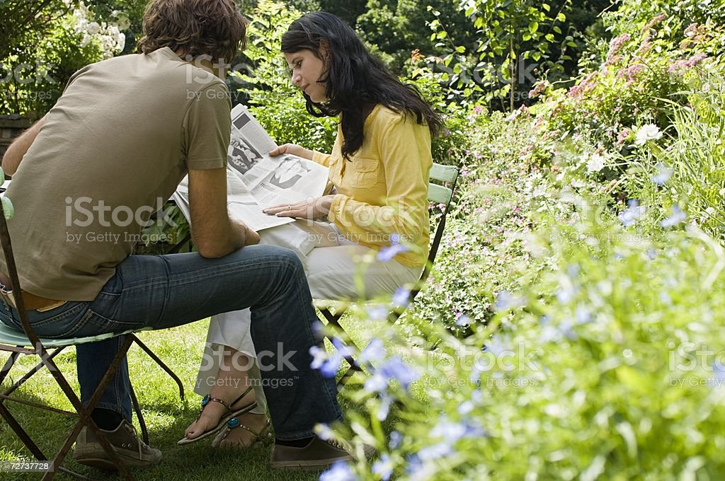 Couple reading newspaper in garden royalty-free stock photo