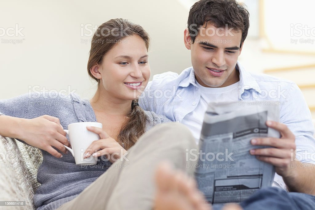Couple reading the news while lying on a sofa stock photo