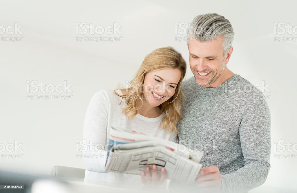 Couple reading the newspaper stock photo