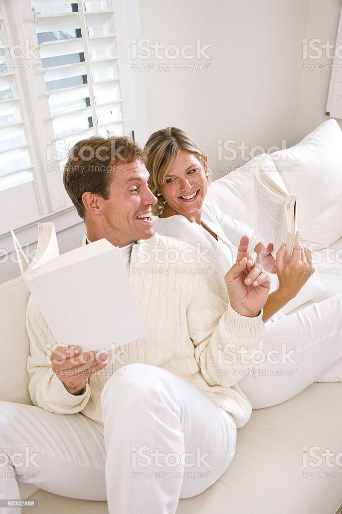 Pareja leyendo juntos en SOFÁ blanco foto de stock libre de derechos