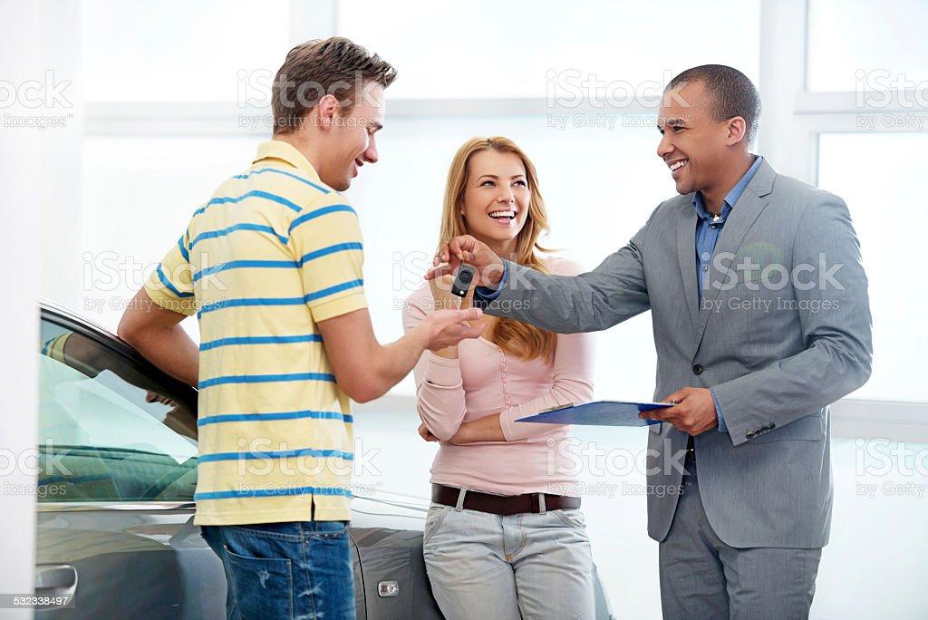 Couple receiving a new car keys stock photo