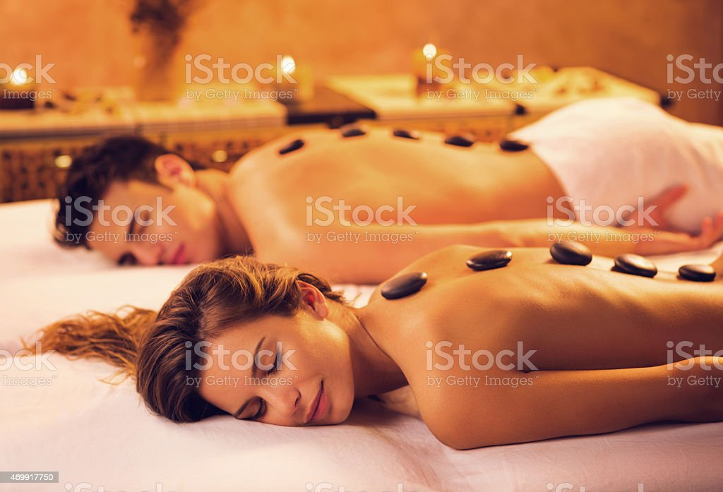 Couple receiving hot stone therapy at the spa. stock photo