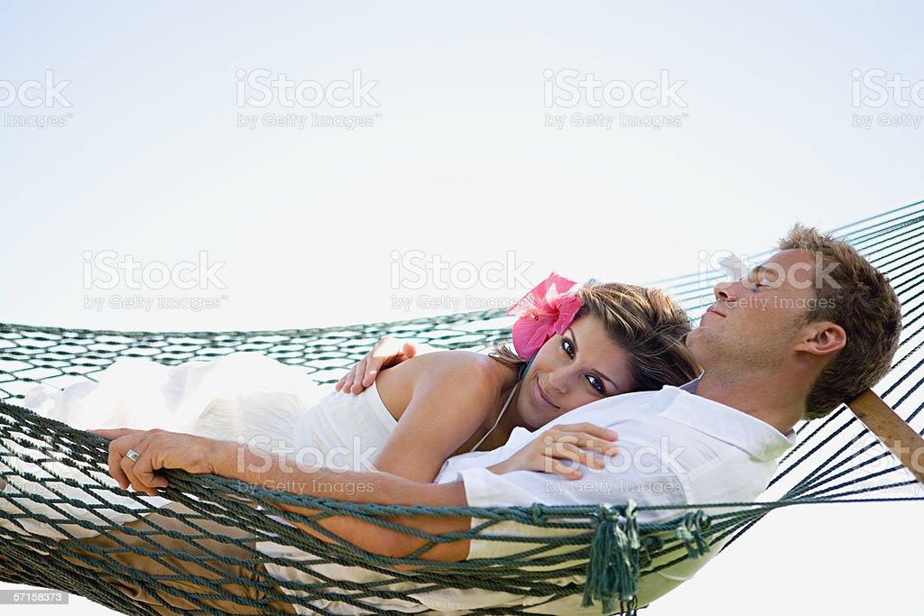 Couple reclining in hammock stock photo