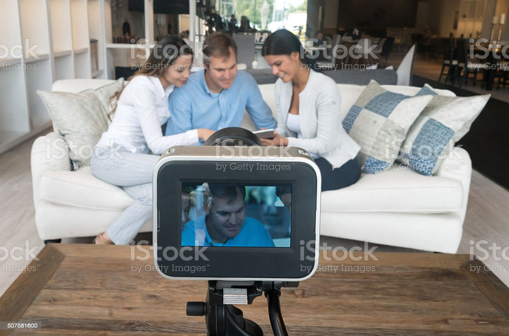 Couple recording a commercial at a furniture store stock photo