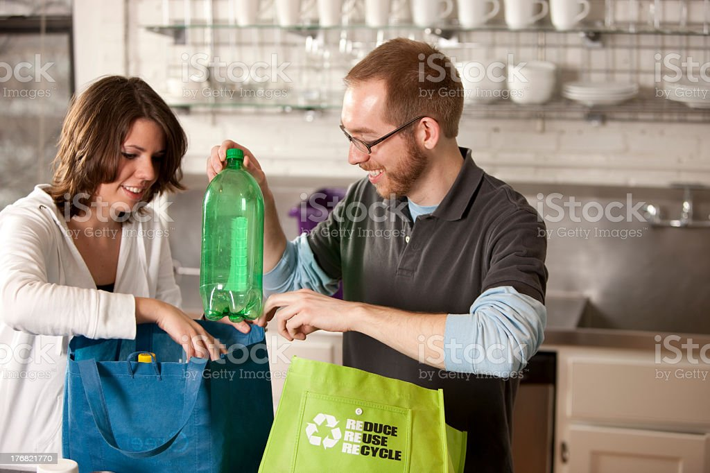 A couple recycling bottles in the kitchen stock photo