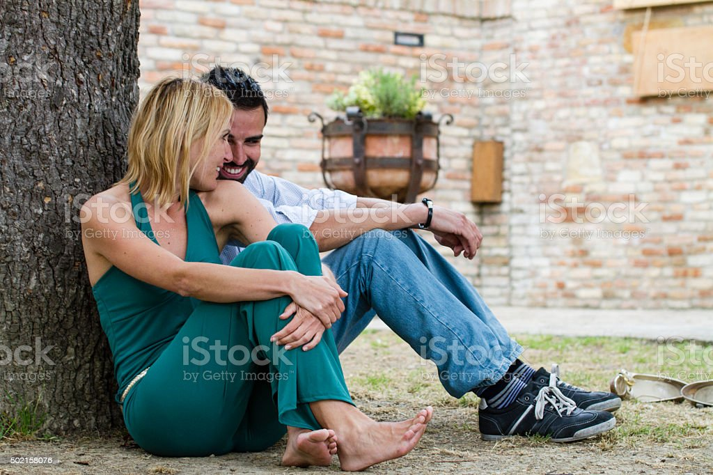 Couple Relaxes Sitting under the Shade of a Tree stock photo