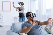 Couple relaxing at home using VR glasses