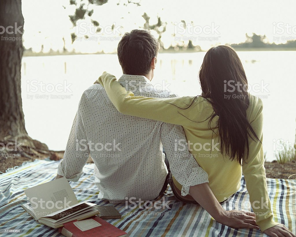A couple relaxing by a shoreline royalty-free stock photo