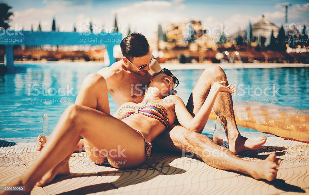 Couple relaxing by swimming pool. stock photo