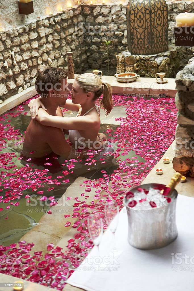 Couple Relaxing In Flower Petal Covered Pool At Spa royalty-free stock photo