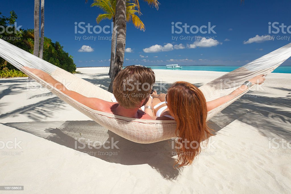 couple relaxing in hammock on sandy beach royalty-free stock photo