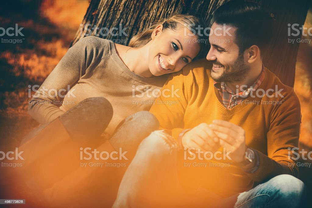 Couple relaxing in park on warm and sunny November day. stock photo