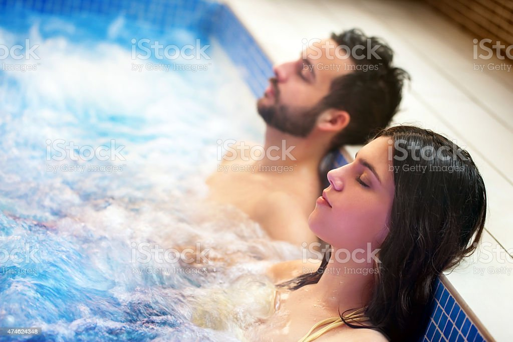 Couple relaxing in spa jacuzzi. stock photo