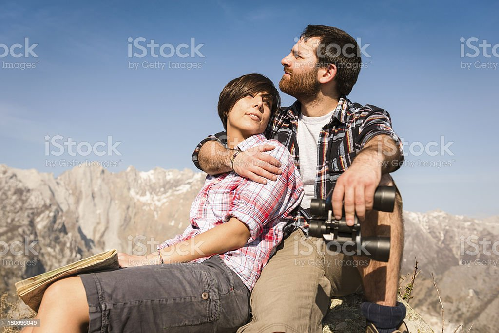 Couple relaxing in the mountain sitting on top of royalty-free stock photo