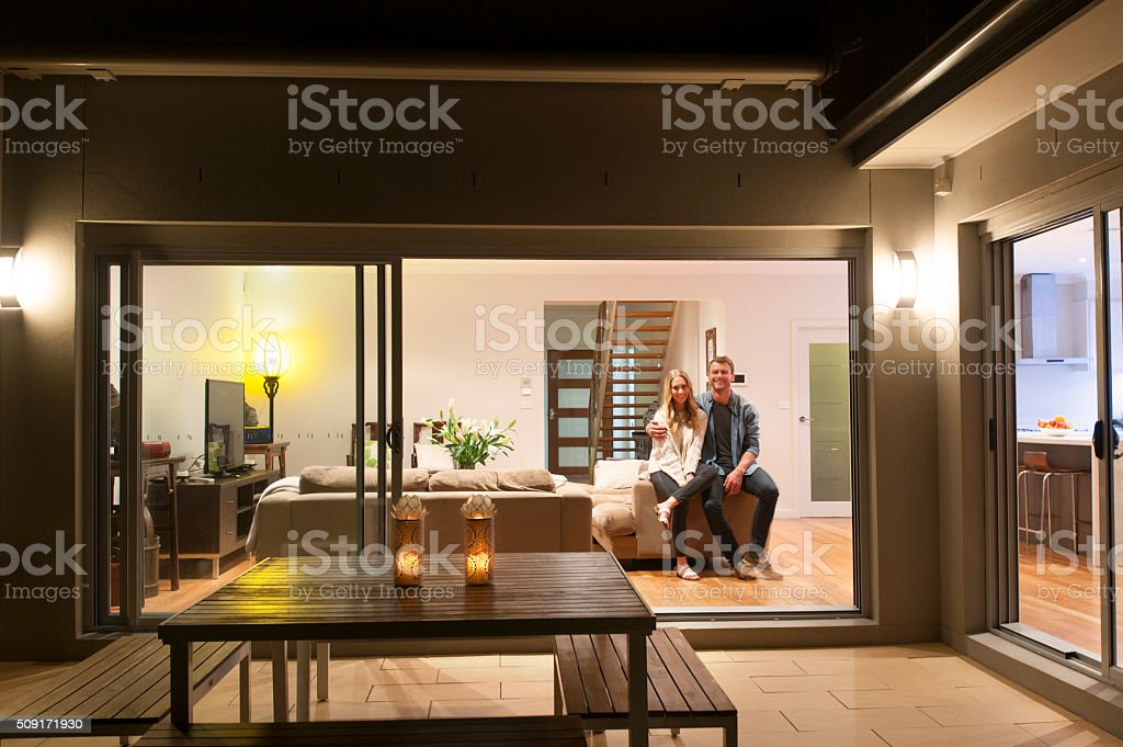 Couple relaxing in their home at night. stock photo
