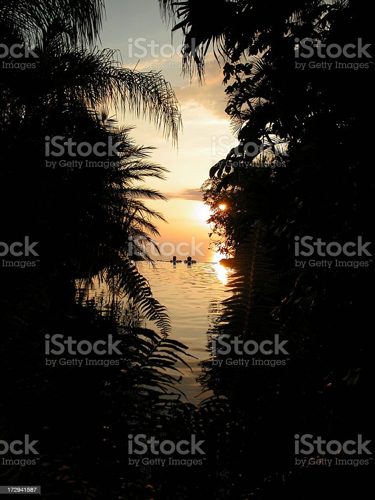 Couple Relaxing Infinity Pool at Tropical Luxury Resort at Sunset royalty-free stock photo