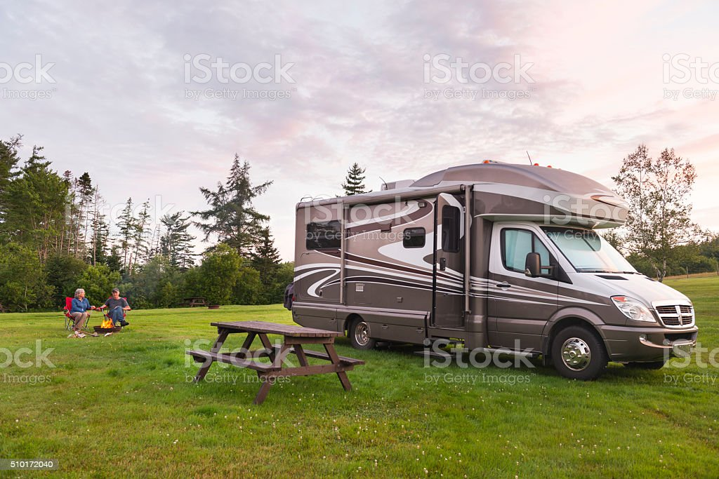 Couple relaxing near campfire and motor home at dusk stock photo