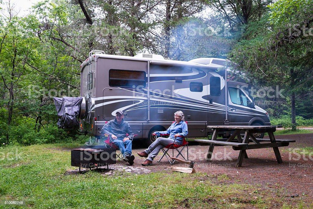 Couple relaxing near campfire stock photo