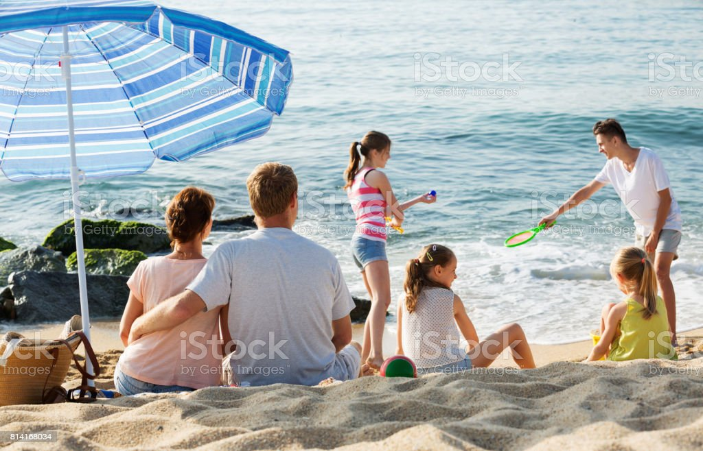 Couple relaxing on beach while their kids playing active games stock photo