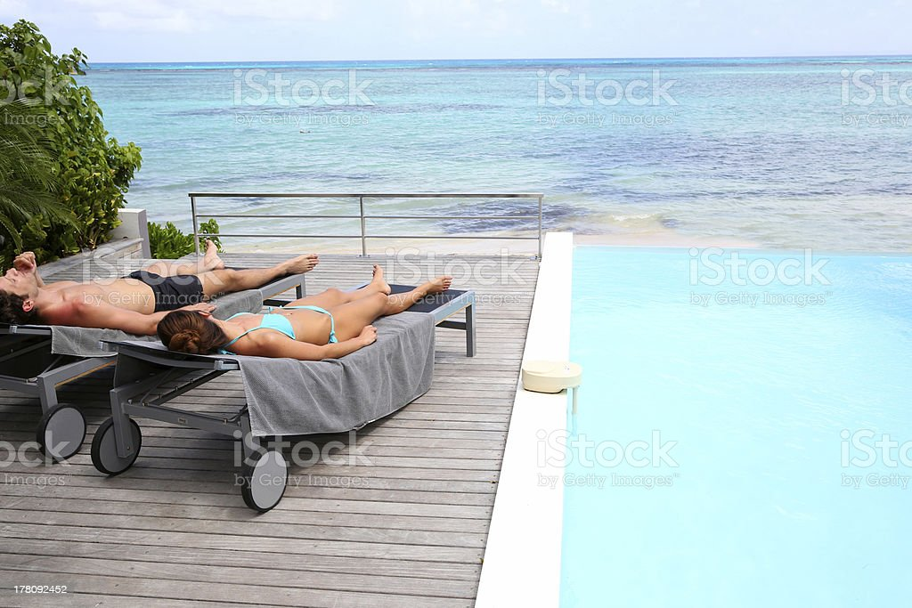 Couple relaxing on deckchair near sea royalty-free stock photo