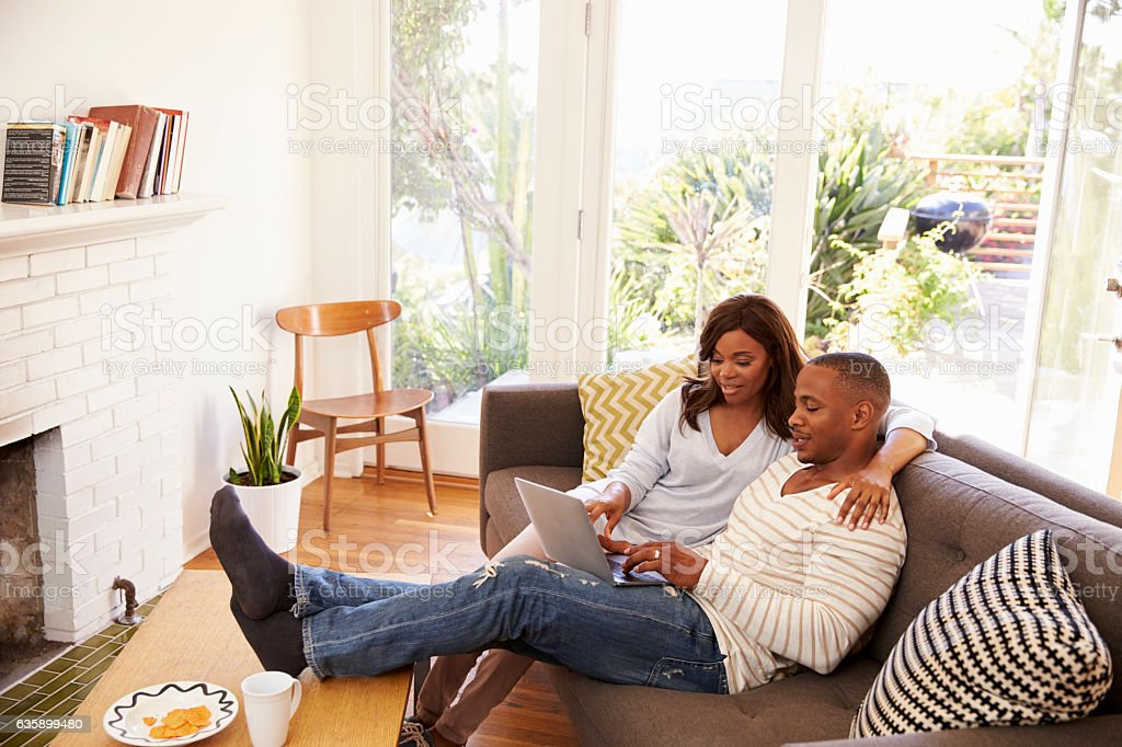 Couple Relaxing On Sofa At Home Using Laptop stock photo