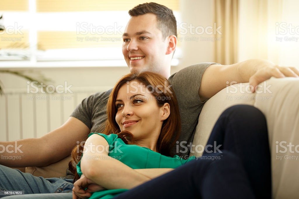 Couple relaxing on sofa in their new home stock photo