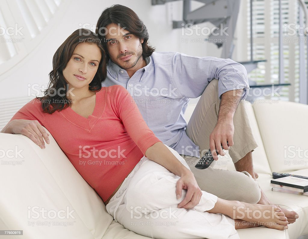 Couple relaxing on sofa with television remote stock photo