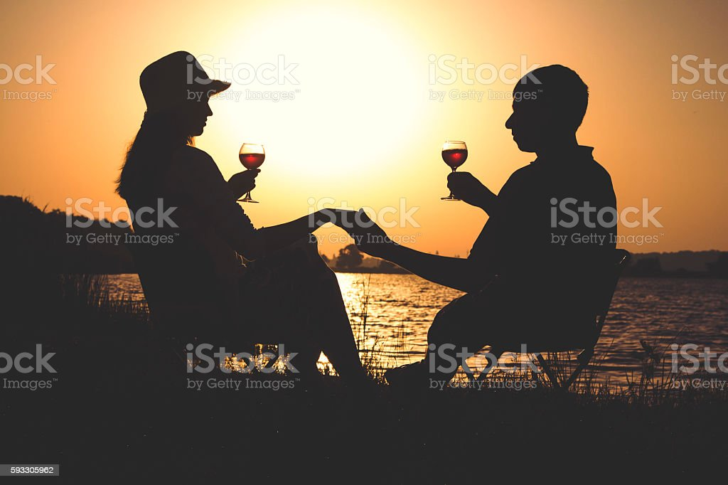 couple relaxing on the bank of the river stock photo