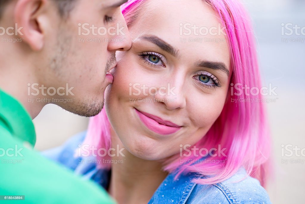 Couple relaxing outdoors, he is kissing his girlfriend stock photo