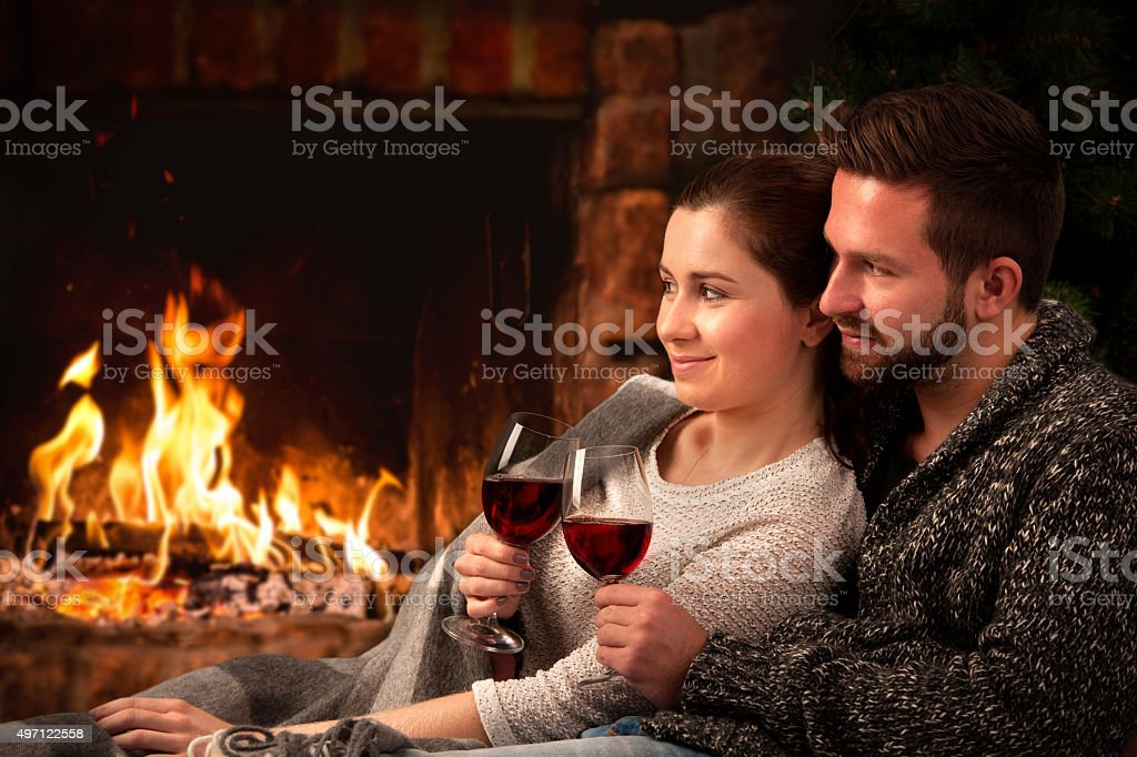 Couple relaxing with glass of wine at fireplace stock photo