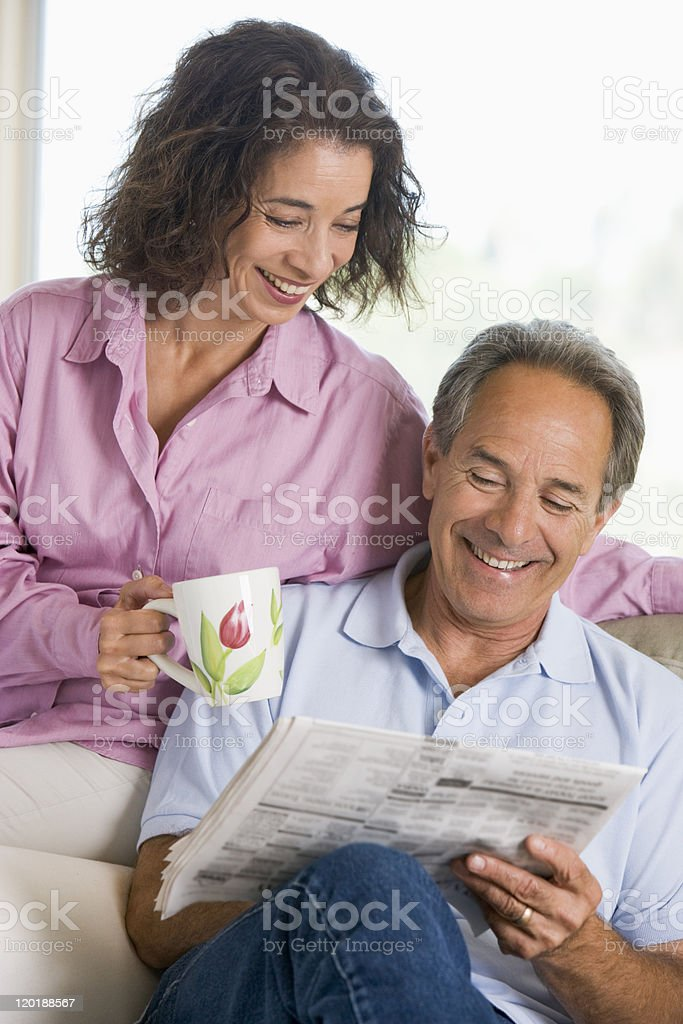 Couple relaxing with newspaper smiling royalty-free stock photo