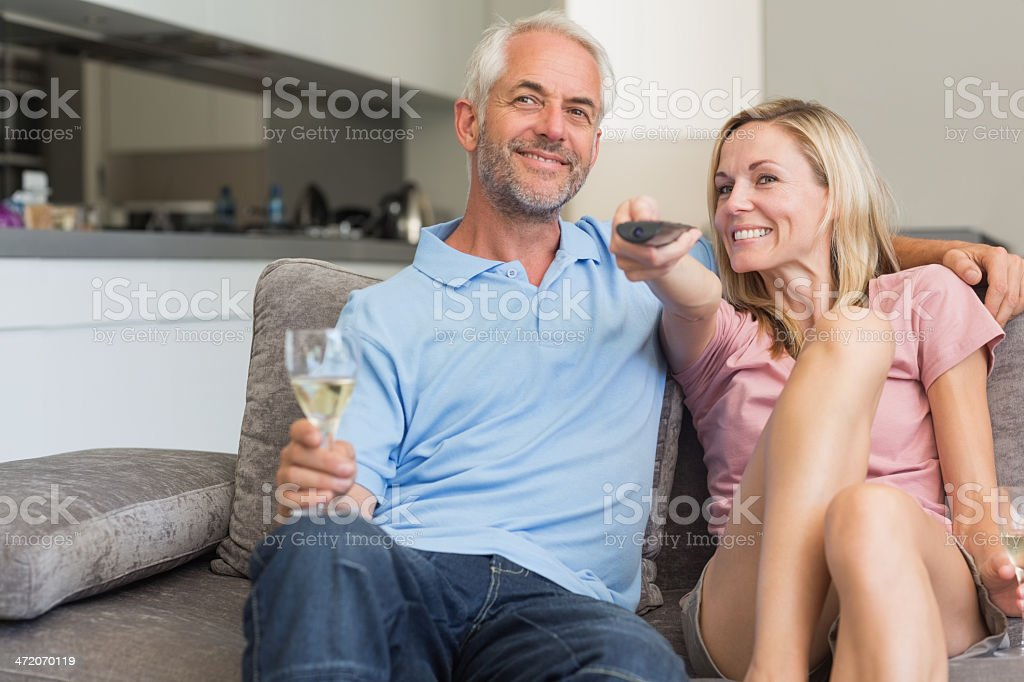 Couple relaxing with wine and watching tv royalty-free stock photo