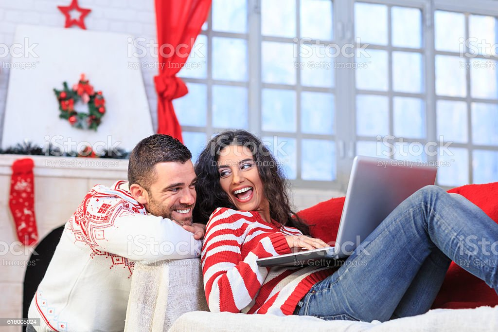Couple resting at home and using laptop stock photo