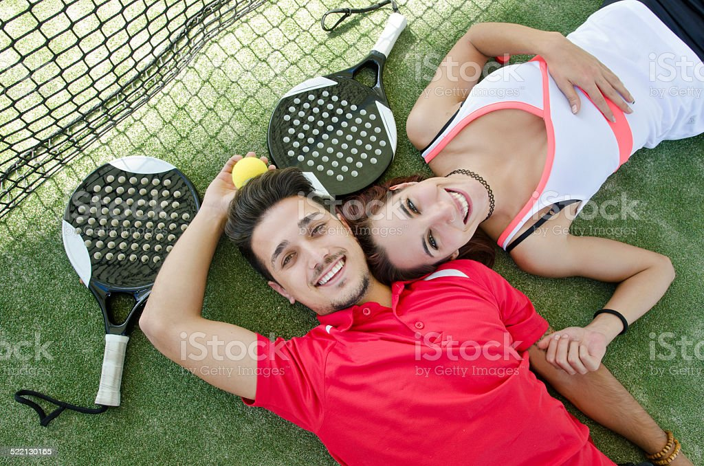 Couple resting in paddle tennis court stock photo