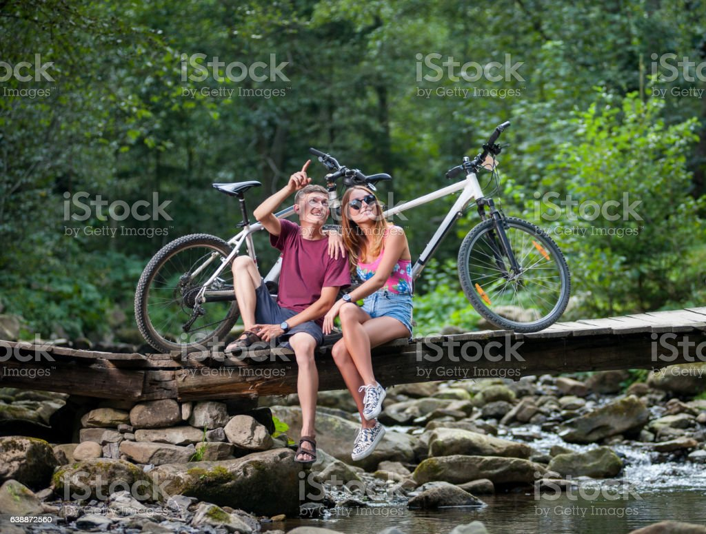 Couple resting in the forest on bridge near bicycles stock photo