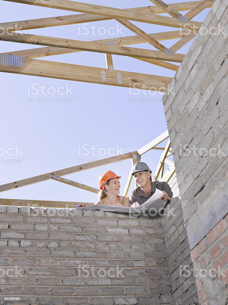 Couple reviewing blueprints at new construction site royalty-free stock photo